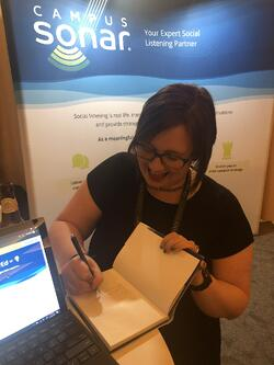 Liz signing books at the Campus Sonar booth at AMA 2019