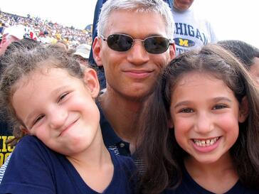 Sarah, her sister, and her dad at their first University of Michigan football game