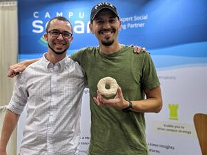 Steve App and Will Patch in front of the Campus Sonar exhibit booth with Steve holding a donut